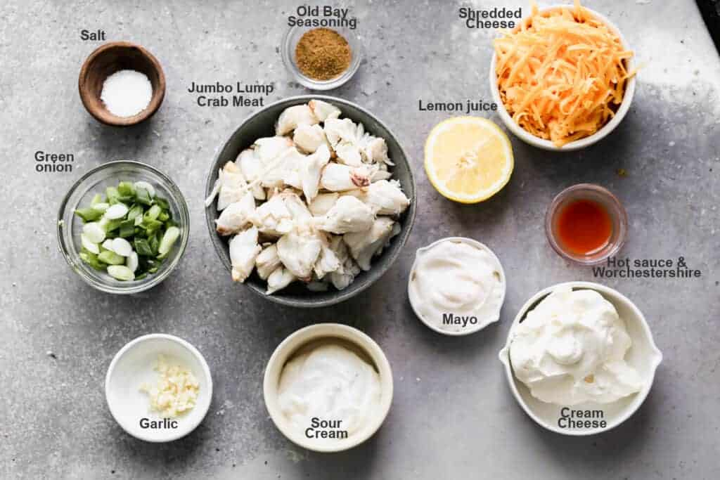 Individual bowls with the ingredients needed to make Crab Dip, labeled.