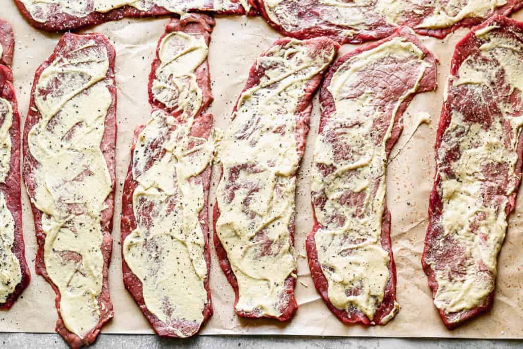Thin sliced of round roast laid on parchment paper with mustard smoothed on top, to make Rouladen.