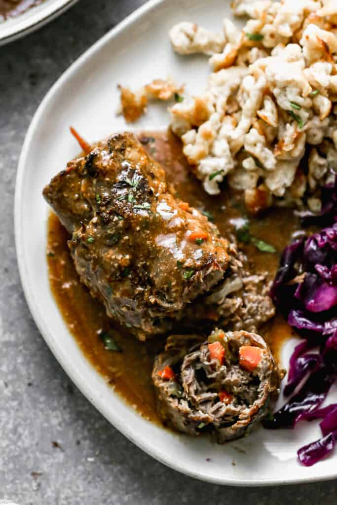 German Rouladen served on a plate with a bite taken out to show the carrot, pickle and onion inside, next to red cabbage and spaetzle.