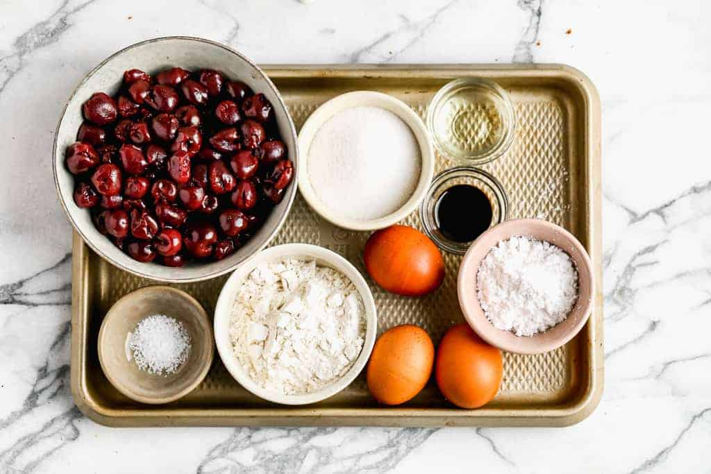 The ingredients for Cherry Clafoutis, including egg, flour, vanilla, cherries, sugar and salt.