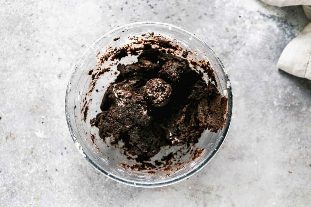 Oreo cookie crumbs mixed with cream cheese in a mixing bowl.