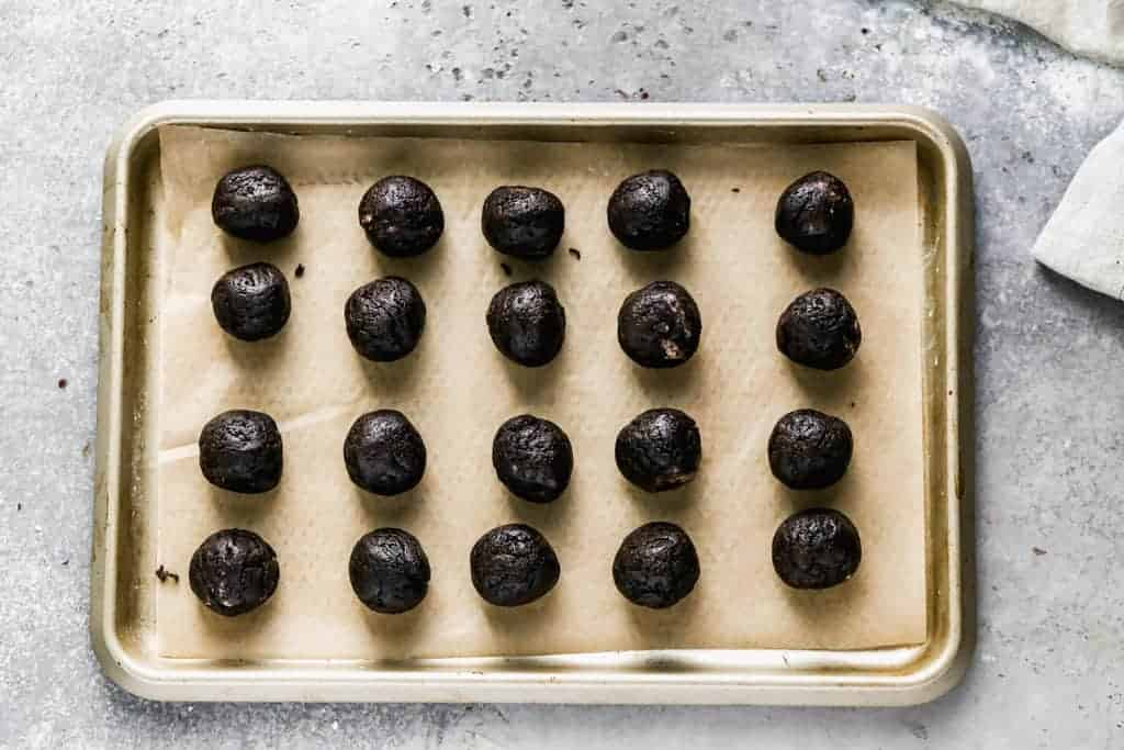 Oreo Balls rolled and placed on a tray.